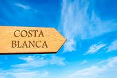 image of costa blanca  - Wooden arrow sign pointing destination COSTA BLANCA SPAIN against clear blue sky with copy space available - JPG