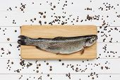 pic of peppercorns  - Trout fish on cutting wooden board with peppercorns - JPG