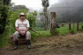 stock photo of vaquero  - Wide angle shot of Costa Rican ranch hand by the side of the road - JPG