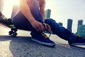 image of skate board  - young skateboarder tying shoelace at skate park - JPG