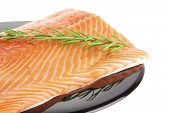 stock photo of fresh water fish  - raw fresh uncooked salmon red fish fillet on black plate with rosemary twig isolated over white background - JPG