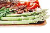 stock photo of white asparagus  - hot lunch of fresh beef meat roasted ribs with asparagus and tomatoes isolated over white background - JPG