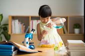 picture of reagent  - Curious Vietnamese girl pouring reagent into flask - JPG