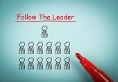 image of leader  - Follow the leader concept is on blue paper with a red marker aside - JPG