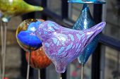 stock photo of water bird  - Glass blown birds displayed outside a shop Bourton on the Water Gloucestershire England UK Western Europe.