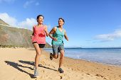 Runners running on beach. Jogging couple training on beach in full body length living healthy active poster