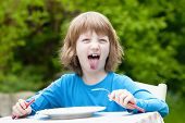 image of sticking out tongue  - Blond Boy Eating Sticking out his Tongue - JPG