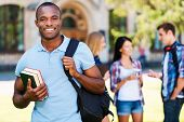 picture of mans-best-friend  - Handsome young African man holding book and smiling while standing against university with his friends chatting in the background  - JPG