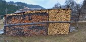 stock photo of firewood  - Stack of firewood in front of an old farm - JPG