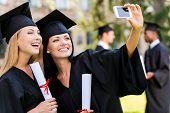 stock photo of graduation gown  - Two happy women in graduation gowns making selfie and smiling while two men standing in the background