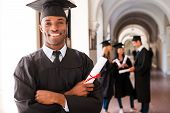 stock photo of graduation gown  - Happy African man in graduation gowns holding diploma and smiling while his friends standing in the background - JPG