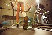 stock photo of treadmill  - Fit girl running on treadmill in gym - JPG