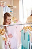 stock photo of blouse  - Attractive woman looking for new blouse in clothing department - JPG