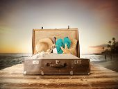 image of mole  - Travel concept with old suitcase on wooden planks full of beach accessories - JPG