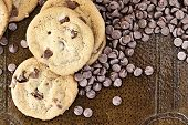 stock photo of chocolate-chip  - Chocolate chips cookies with loosely scattered chocolate chips over a rustic background - JPG