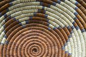 stock photo of sun-tanned  - A close up photo of a Native American Indian basket woven in browns and tan with purple outline - JPG