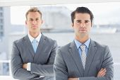image of frown  - Two businessmen frowning at camera in the office - JPG