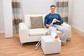 pic of crutch  - Portrait Of A Smiling Man Sitting On Sofa With Crutches At Home - JPG