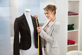 picture of measurements  - Portrait Of Fashion Designer Measuring Suit With Measuring Tape - JPG