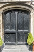 stock photo of stud  - Medieval wooden studded double door with ancient stone surround - JPG