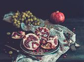 image of pomegranate  - Red ripe peeled pomegranate on rustic metal plate and beige kitchen towel over dark background - JPG