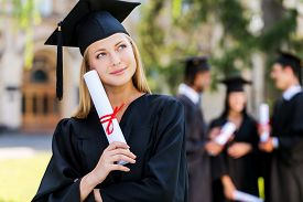 stock photo of graduation gown  - Thoughtful young woman in graduation gowns holding diploma and looking away while her friends standing in the background