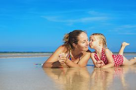 image of children beach  - Small child playing with fun and kissing happy young mother smiling with love to her daughter lying on wet sand sea beach - JPG