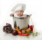 picture of chefs hat  - Portrait of a smiling baby sitting wearing a chef hat sitting inside a large cooking stock pot surrounded by vegetables and food - JPG