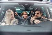 Picture of emotional young man sitting in car with his funny wife and daughter. Looking at each othe poster