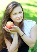 pretty young girl with an apple in summer park enjoying