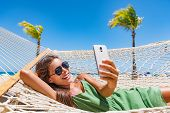 Summer beach lifestyle young woman using phone app texting on smartphone relaxing at tropical Caribb poster