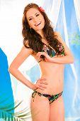 Laughing beautiful young girl in bikini with flower in hair posing in summerhouse on beach.