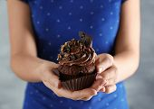 Woman holding tasty chocolate cupcake, closeup poster