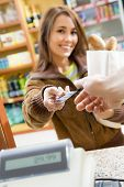 foto of cash register  - woman doing shopping in a grocery store and paying by credit card