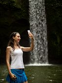 Lifestyle Travel Blogger. Happy Caucasian Woman Enjoying Waterfall Landscape In Tropic, Taking Selfi poster