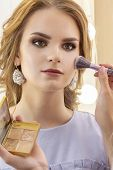 Makeup Artist Puts Makeup On Girl Model. Brush Powder On Cheekbones And Face. Beautiful Girl Model,  poster