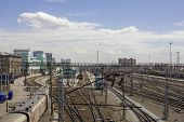 Railway Station With A Lot Of Railway Tracks And Modern Trains In The Background Of City Buildings poster