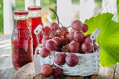 A Bunch Of Pink Grapes, Prepared To Extract The Juice, Is In A White Basket . Two Bottles Of Grape J poster
