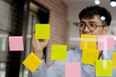 Young Asian Businessman Writing On Sticky Note At Office, Business Brainstorming Creative Ideas, Asi poster