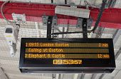 Electronic Timetable on London Railway Platform with Security Camera
