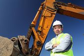 image of heavy equipment operator  - portrait operator of excavator standing on location site with clear sky background - JPG
