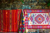 Carpets Embroidered From Threads Of Various Bright Colors. Carpets Are Hung On A Stone Wall In A Tur poster