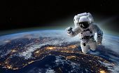 Astronaut at spacewalk. Concept of conquering the universe by the human race. Elements of this image poster
