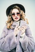 A portrait of a beautiful woman wearing a fur coat and a hat and sunglasses. Beauty, winter fashion, poster