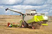 Combine Harvester On Wheat Field Harvesting Grain. Agricultural Scene. Harvest Time poster