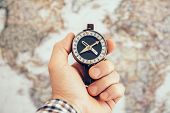 Close Up Of Man Hand Holding Vintage Compass With World Map As Background. Travel And Business Plann poster