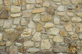 A Stone Wall Or Building Exterior Made Of Stones Of Different Sizes, Shapes, And Shades Of Brown Cre poster