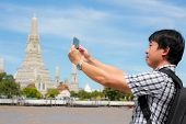 Tourists Holding A Mobile Phone To Take Pictures Yourself Smiling With Wat Arun At Thailand. poster