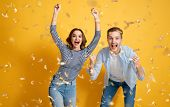 Young joyful couple on yellow background with golden confetti. poster