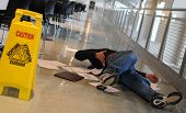 stock photo of beside  - A man who slipped on a wet floor beside a bright yellow caution sign holds his back in pain